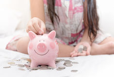 Τεθειμένα χέρι χρήματα κοριτσιών στο piggybank στην κρεβατοκάμαρα Στοκ φωτογραφίες με δικαίωμα ελεύθερης χρήσης