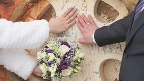 Τεθειμένα Newlyweds χέρια με τα δαχτυλίδια στον τοίχο της εκκλησίας φιλμ μικρού μήκους