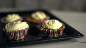 Τεθειμένος αρχιμάγειρας cupcakes δίσκος στον άσπρο πίνακα Muffin κέικ με την άσπρη κρέμα φιλμ μικρού μήκους