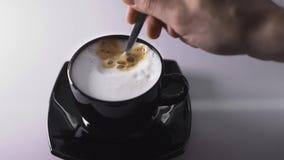 Τεθειμένος για να προσθέσει τη σοκολάτα μέσα στον καυτό καφέ στο μαύρο φλυτζάνι απόθεμα βίντεο