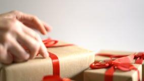 Τεθειμένος και τακτοποιήστε το κιβώτιο δώρων Χριστουγέννων στο άσπρο υπόβαθρο απόθεμα βίντεο