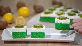 Τεθειμένος στο άσπρο πράσινο μαλακό κέικ πιάτων με την κτυπώντας κρέμα και το κάλυμμα με το ακτινίδιο φιλμ μικρού μήκους