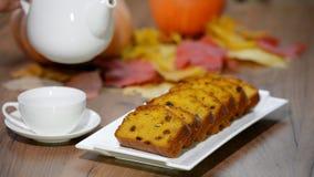 Τεθειμένος στο πιάτο τεμάχισε το γλυκό ψωμί κολοκύθας Χύστε το τσάι στο φλυτζάνι φιλμ μικρού μήκους