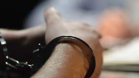 Τεθειμένος υπό κράτηση κλέφτης που απαντά στις ερωτήσεις δικηγόρων στο αστυνομικό τμήμα, χειροπέδες κοντά επάνω απόθεμα βίντεο