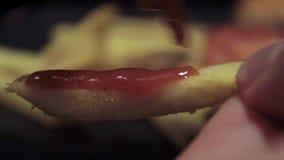 Τεθειμένος catchup στα τσιπ πατατών τηγανιτών πατατών με μια σύριγγα Σε αποκριές απόθεμα βίντεο