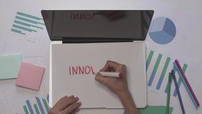 Τεθειμένο το γυναίκα έγγραφο για το lap-top και γράφει την ΚΑΙΝΟΤΟΜΙΑ Επιχειρησιακός υπολογιστής γραφείου με τα διαγράμματα φιλμ μικρού μήκους