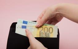Τεθειμένο χέρια ευρώ γυναικών στο μαύρο φάκελο στο ρόδινο υπόβαθρο Επιχειρησιακά έννοια και Instagram Στοκ εικόνες με δικαίωμα ελεύθερης χρήσης