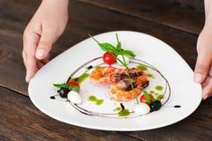 Τεθειμένο χέρια πιάτο σερβιτόρων με τις γαρίδες στο σκοτεινό πίνακα Στοκ φωτογραφίες με δικαίωμα ελεύθερης χρήσης
