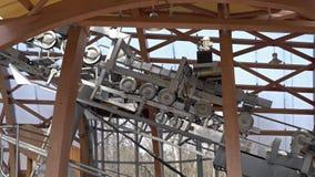 Τελεφερίκ μηχανισμός μετάλλων με τις περιστρεφόμενες ρόδες Ανυψωτικός ανελκυστήρας στο βουνό φιλμ μικρού μήκους