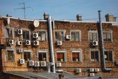 Τεμάχιο ενός σπιτιού τούβλου με τις δορυφορικά κεραίες και τα κλιματιστικά μηχανήματα στοκ εικόνα με δικαίωμα ελεύθερης χρήσης