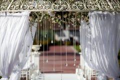 Τεμάχιο της δημιουργικά διακοσμημένης γαμήλιας αψίδας υπαίθρια Στοκ Φωτογραφία