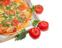 Τεμάχιο της μαγειρευμένης πίτσας στο κουτί από χαρτόνι και τις ντομάτες Στοκ Εικόνα