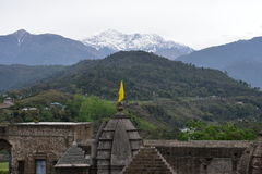 Τεμάχιο του αρχαίου ναού Shiva σε Baijnath, Himachal Pradesh, Ινδία με τους πράσινους λόφους και τα χιονώδη βουνά στο σκηνικό Στοκ φωτογραφία με δικαίωμα ελεύθερης χρήσης