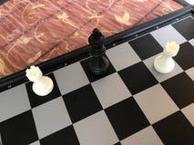 Τεμάχιο του κόμματος σκακιού οι αριθμοί είναι στον πίνακα το χαλί έβαλε το μαύρο βασιλιά Στοκ Εικόνα