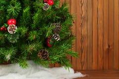 Τεμάχιο του πράσινου διακοσμημένου χριστουγεννιάτικου δέντρου στο ξύλινο υπόβαθρο Στοκ Φωτογραφία