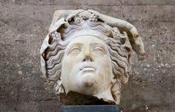 Τεμάχιο του ρωμαϊκού αγάλματος - Θεός από αρχαίο Corinth Ελλάδα με τα λουλούδια ή τα σταφύλια στην κυματιστή τρίχα και μέρος ενός Στοκ Εικόνα