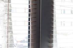 Τεμάχιο των άσπρων ενετικών τυφλών με το σκοινί ανελκυστήρων και ράβδος στροφής ενός χειρωνακτικού ελέγχου σε ένα πρώτο πλάνο στοκ φωτογραφία