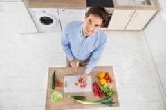 Τεμαχίζοντας λαχανικά ατόμων στην κουζίνα Στοκ Εικόνα