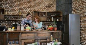Τεμαχίζοντας λαχανικά γυναικών που χρησιμοποιούν τη συνταγή στη συζήτηση υπολογιστών ταμπλετών με τον άνδρα, ενήλικο μαγείρεμα ζε φιλμ μικρού μήκους