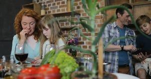Τεμαχίζοντας λαχανικά μητέρων και κορών ενώ πατέρας με το γιο που χρησιμοποιεί τον υπολογιστή ταμπλετών, ευτυχής οικογένεια που μ απόθεμα βίντεο