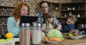 Τεμαχίζοντας λαχανικά πατέρων και κορών που μαγειρεύουν μαζί στην κουζίνα που μιλά με το γιο ενώ μητέρα που χρησιμοποιεί την ταμπ φιλμ μικρού μήκους