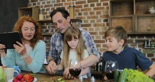 Τεμαχίζοντας λαχανικά πατέρων και κορών που μαγειρεύουν μαζί στην κουζίνα που μιλά με το γιο ενώ μητέρα που χρησιμοποιεί την ταμπ απόθεμα βίντεο