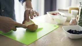 Τεμαχίζοντας κρεμμύδι ατόμων στον τεμαχίζοντας πίνακα στην κουζίνα σε αργή κίνηση φιλμ μικρού μήκους