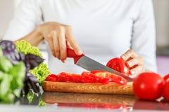 Τεμαχίζοντας ντομάτες νεαρών άνδρων με ένα αιχμηρό μαχαίρι Η έννοια είναι Στοκ Εικόνα