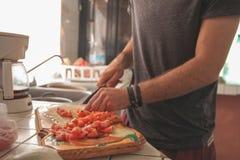 Τεμαχίζοντας ντομάτες νεαρών άνδρων Στοκ Φωτογραφία