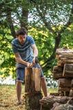 Τεμαχίζοντας ξύλο ατόμων με ένα τσεκούρι Στοκ Εικόνες