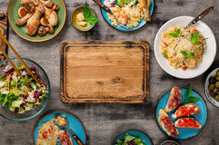 Τεμαχίζοντας πίνακας, risotto, ψημένα πόδια κοτόπουλου και πρόχειρα φαγητά Στοκ φωτογραφίες με δικαίωμα ελεύθερης χρήσης