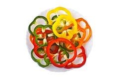 Τεμαχισμένα γλυκά ζωηρόχρωμα πιπέρια σε ένα πιάτο πέρα από το λευκό Στοκ εικόνα με δικαίωμα ελεύθερης χρήσης
