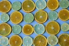 Τεμαχισμένα δαχτυλίδια του πορτοκαλιού, λεμόνι, ασβέστης στο μπλε υπόβαθρο r , detox, διατροφή στοκ εικόνες