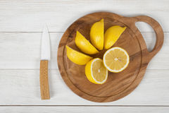 Τεμαχισμένα και ολόκληρα λεμόνια στον τέμνοντα πίνακα με ένα μαχαίρι δίπλα σε το κατά τη τοπ άποψη Στοκ εικόνες με δικαίωμα ελεύθερης χρήσης
