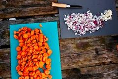 Τεμαχισμένα καρότα και κόκκινα κρεμμύδια σε έναν ξύλινο πίνακα κατά τη διάρκεια της στρατοπέδευσης και έναν υπαίθριο σουγιά στην  Στοκ Εικόνα