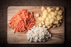 Τεμαχισμένα κρεμμύδια, καρότα, πατάτες που συσσωρεύονται στις ομάδες σχετικά με έναν ξύλινο Στοκ Εικόνες