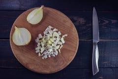 Τεμαχισμένα κρεμμύδια με το μαχαίρι στον ξύλινο τέμνοντα πίνακα, τοπ άποψη Στοκ Φωτογραφία