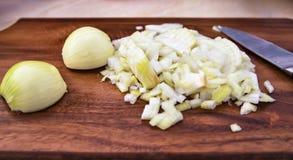Τεμαχισμένα κρεμμύδια στον ξύλινο τέμνοντα πίνακα Στοκ Φωτογραφίες