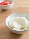 Τεμαχισμένα κρεμμύδια στο άσπρο κύπελλο στον ξύλινο πίνακα Στοκ Εικόνα