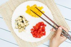 Τεμαχισμένα λαχανικά στο χαλί μπαμπού Χέρια chopstick εκμετάλλευσης κοριτσιών Τοπ άποψη σχετικά με τον ξύλινο πίνακα Στοκ Εικόνες