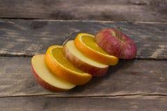 Τεμαχισμένα μήλο και πορτοκάλι στις ξύλινες γέφυρες Στοκ Φωτογραφία