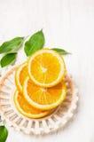 Τεμαχισμένα πορτοκάλια με τα φύλλα στο κύπελλο άσπρο σε ξύλινο Στοκ φωτογραφία με δικαίωμα ελεύθερης χρήσης