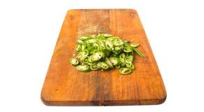 Τεμαχισμένα πράσινα πιπέρια τσίλι στον τεμαχίζοντας πίνακα Β Στοκ Εικόνες
