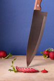 Τεμαχισμένα ραδίκια στον τέμνοντα πίνακα, μαχαίρι κουζινών Κλείστε επάνω, μπλε υπόβαθρο στοκ εικόνα