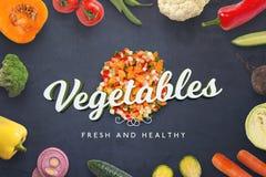 Τεμαχισμένα φρέσκα λαχανικά και τρισδιάστατο κείμενο στη μαύρη επιφάνεια κουζινών Στοκ Φωτογραφία