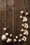 τεμαχισμένα champignon μανιτάρια στην πλάκα και το ξύλινο αντίθετο τοπ υπόβαθρο Στοκ φωτογραφία με δικαίωμα ελεύθερης χρήσης