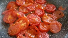Τεμαχισμένες ντομάτες σε ένα τηγανίζοντας τηγάνι απόθεμα βίντεο