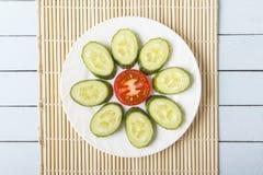 Τεμαχισμένες οργανικές αγγούρι και ντομάτα σε ένα άσπρο πιάτο υπό μορφή λουλουδιού υγιής χορτοφάγος τροφίμων Τοπ όψη Στοκ Εικόνες