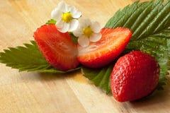 Τεμαχισμένες φράουλες σε ένα φύλλο με το λουλούδι στοκ εικόνες με δικαίωμα ελεύθερης χρήσης
