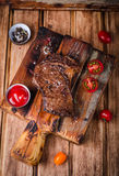 Τεμαχισμένη μέση σπάνια ψημένη στη σχάρα μπριζόλα βόειου κρέατος με τα καρυκεύματα και κέτσαπ στον τέμνοντα πίνακα στο ξύλινο υπό Στοκ Εικόνες